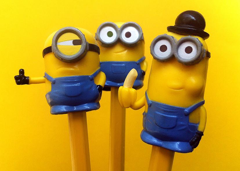 Drie plastic figuurtjes in de vorm van minions, op de achterkant van een potlood geschoven. Promotiemateriaal.