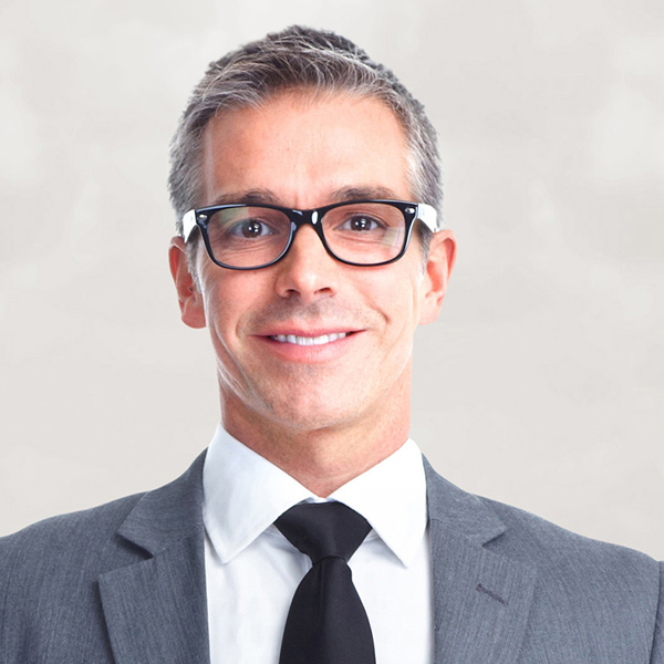 Businessman in glasses in grey suit smiling