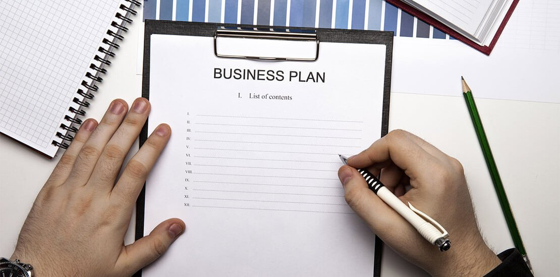 Business plan headed paper on clip board with man holding pen