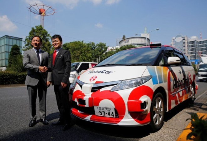 Hinomaru Kotsu Co's President and CEO Kazutaka Tomita and ZMP Inc's CEO Hisashi Taniguchi shake hands next to ZMP's RoboCar MiniVan, a self-driving Toyota Estima Hybrid car, after their joint news conference in Tokyo