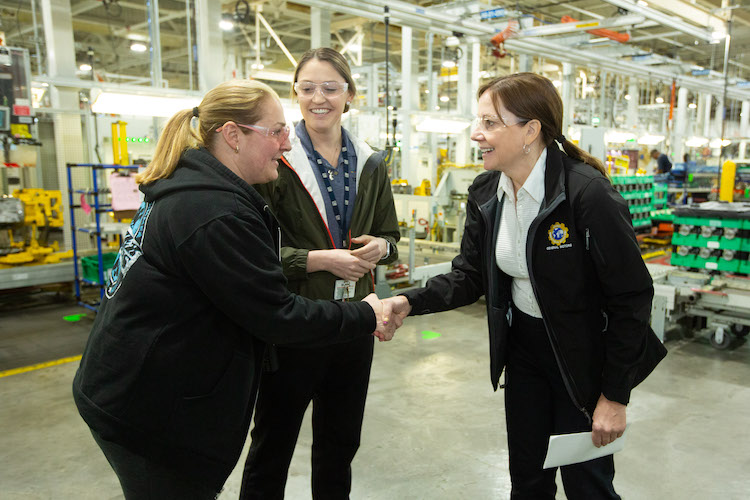 GM CEO Mary Barra talks with employees Angela Jarrett, left, and Kayla Owens at the GM Romulus plant