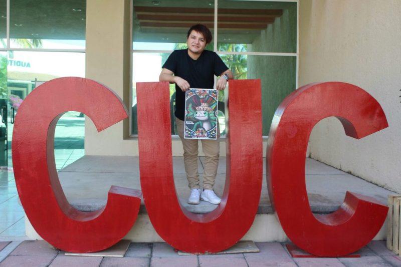 Alejo sosteniendo un póster del videojuego.