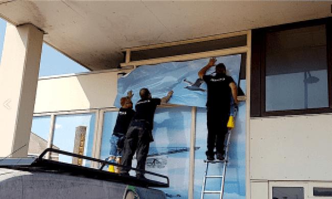 Zeeman Reclamegroep personeel brengt 'kunstig' design aan op de ramen van het Rob Scholte Museum (foto DHA)