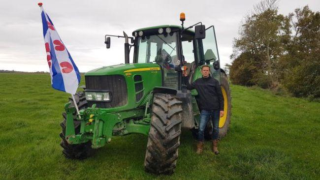 Rob Smit met Friese vlag bij zijn tractor (foto NHD)