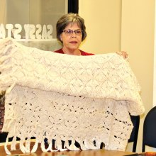 Karen Solomon showing handmade bedspread. Photo courtesy of Andy McConnell