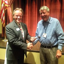 Russ Bafford receiving the gavel from outgoing president Don Kissock