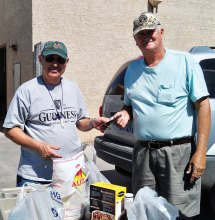 Alan Friedman, left, presenting both cash and donated food items to a representative of the Casa Grande Food Bank after a fundraiser benefiting their organization.