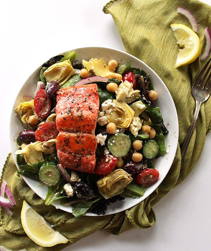 Easy Greek Salmon Salad - Fresh lettuce greens topped with all your Greek fixin's, tossed with a creamy Greek dressing and topped with a hunk of pan seared salmon. This recipe is EASY - perfect for a weeknight meal. Gluten free.