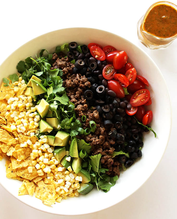 Healthy Taco Salad - Crunchy shredded romaine lettuce piled high with the best taco toppings and drizzled with a salsa lime vinaigrette. This easy recipe is perfect for summer! Gluten Free.