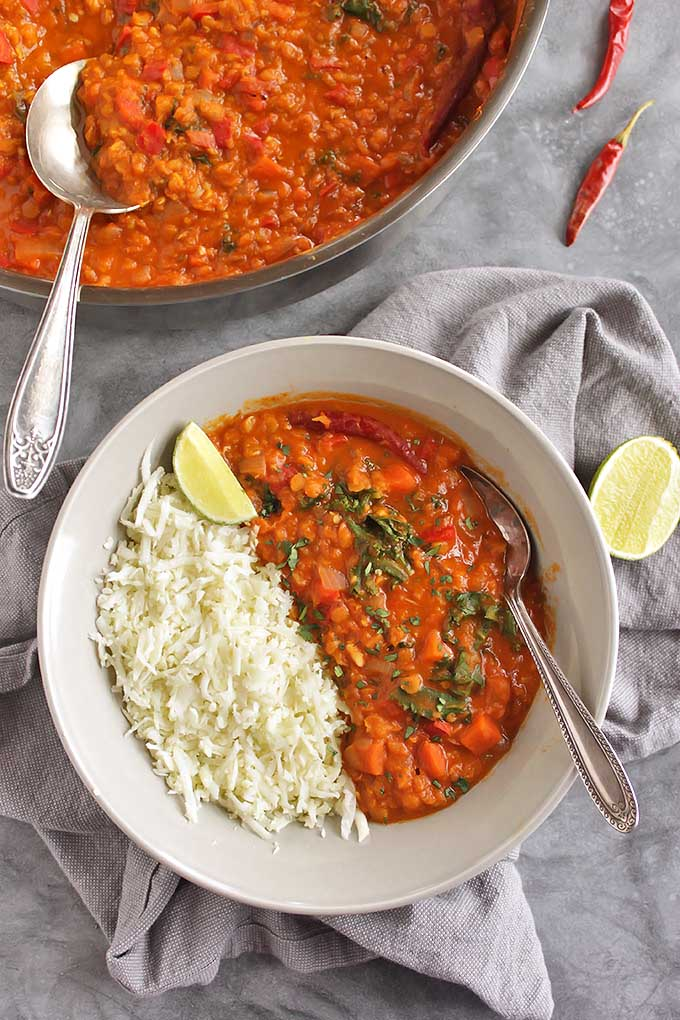 40 Minute Red Lentil Curry with Cauliflower Rice - Warming, creamy, flavorful, and spicy. This recipe is packed with veggies and 13 grams of protein per serving making it a plant based meal that will stick with you for hours. Only takes 40 minutes to make, perfect for a weeknight dinner. Gluten free/vegan/dairy free | robustrecipes.com