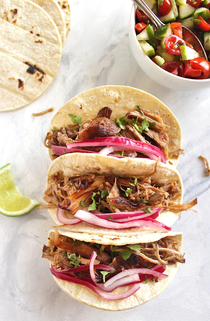 Slow Cooker Spicy Carnitas - Pork cooked until it's melt-in-your-mouth tender and then cooked under a broiler until it crisps up a little. Topped with a simple cucumber tomato pico de gallo and picked onions. This recipe is great for meal prep or feeding a crowd. The pork also freezes really well. Gluten Free/Dairy Free | robustrecipes.com
