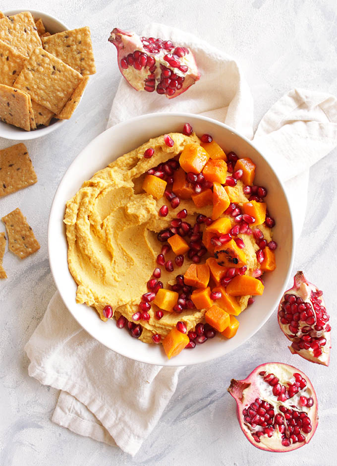 Loaded Butternut Squash Hummus with Pomegranate - Hummus that is packed with roasted butternut squash and topped with more butternut squash chunks and pomegranate seeds. Serve with crackers for dipping. Makes for the perfect Thanksgiving or Christmas appetizer. It's also great because it can mostly be made ahead and served room temperature or cold. (vegan/gluten free) | robustrecipes.com