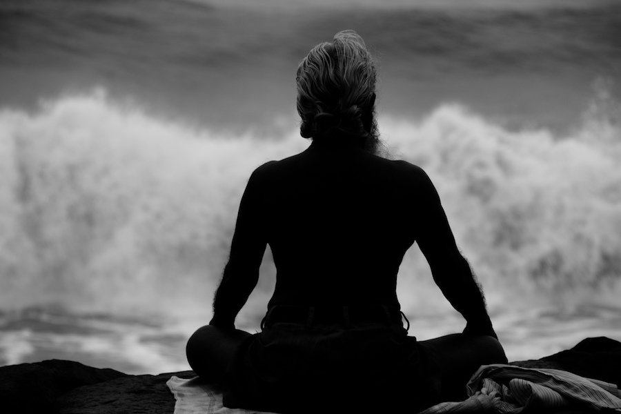 woman meditating by ocean