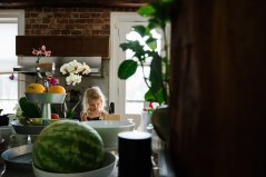 everyday-documentary-tilt-shift-photo-of-little-girl-in-kitchen-with-colorful-summer-fruit-and-flowers-by-sarah-wilkerson