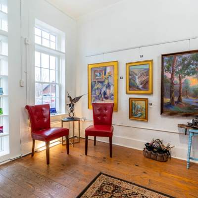 artwork hanging inside the art gallery next to two red chairs