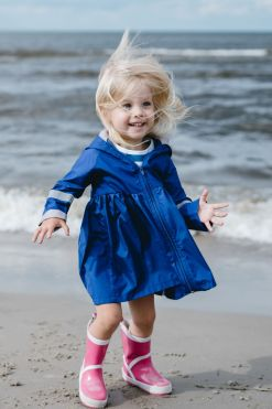 Happy toddler girl , kid on the beach in blue girl summer raincoat and pink rubber boots