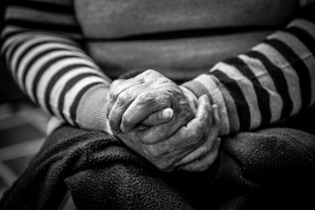 elderly person with their hands folded
