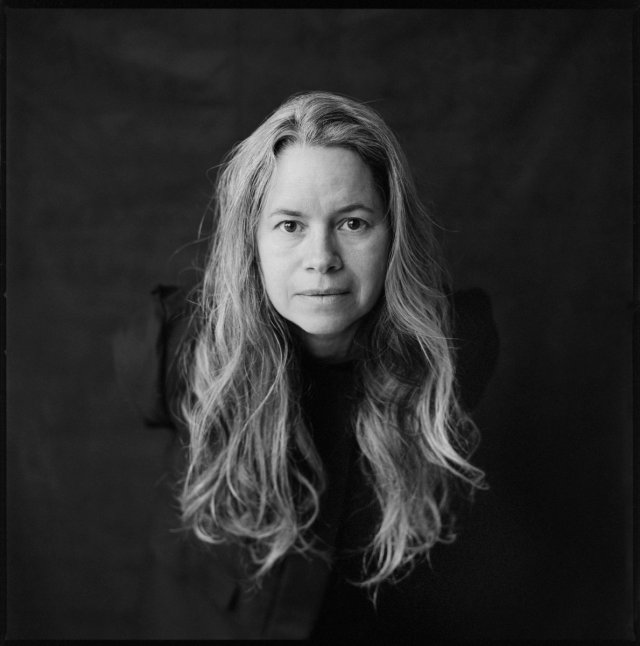Natalie Merchant leaning forward with black background