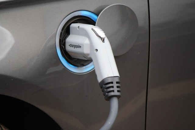 Gray car plugged into electric charger