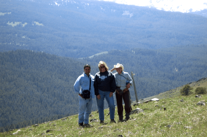 Three People Posing at Top of Mountain