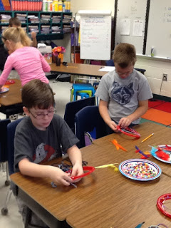 student boy making a Native american dream catcher with beads and feathers.