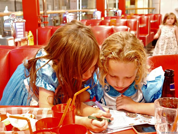 Big girls heads down working on the puzzles which are both on the bag and on the paper kid's menu!