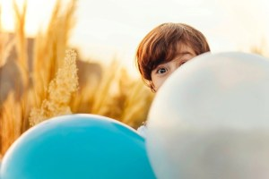 Kid hiding behind balloons waiting for first dental visit