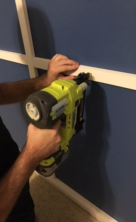 using a nail gun on the diy modern wood accent wall