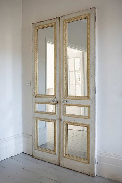 Le Meilleur Pair Of Old Doors With Mirror Inserts Against A Plain Wall Ce Mois Ci