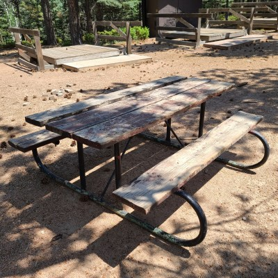 Multiple tables are placed at each campsite so as to be a natural gathering location for the troop.
