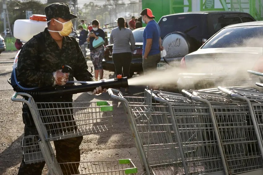 A soldier of the Honduran presidential guard disinfects shopping carts outside a supermarket during a break of the curfew imposed by the government against the spread of the new coronavirus, in Tegucigalpa, on March 19, 2020. (Photo by ORLANDO SIERRA/AFP via Getty Images)