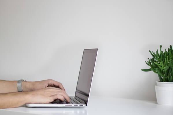 パソコンに文字入力している男性