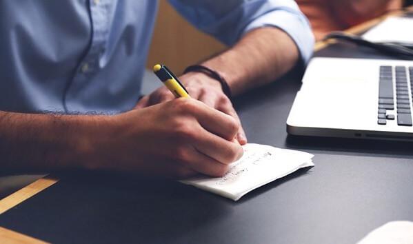 ノートに何か書いている男性