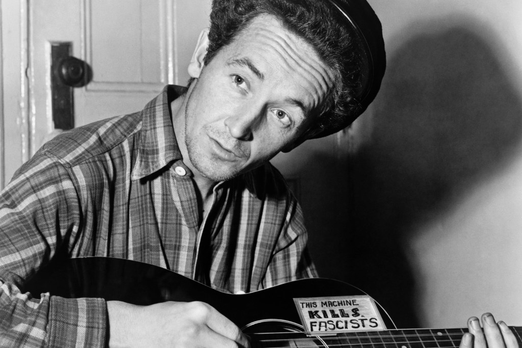 Woody Guthrie (1943) spelar en gitarr med klistermärket: This Machine Kills Fascists.