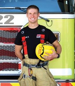 patrick bailey, and EMS RCC success story poses in front of a fire truck