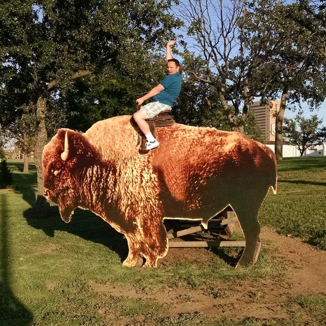 Greg Bellefontaine of Roguetrippers riding a bison in Abilene Texas during a road trip Route66