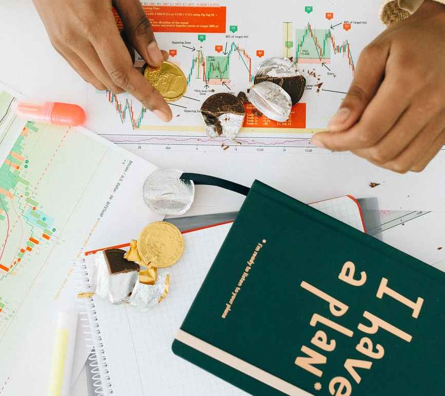 person holding a gold chocolate coin on the table with a green book