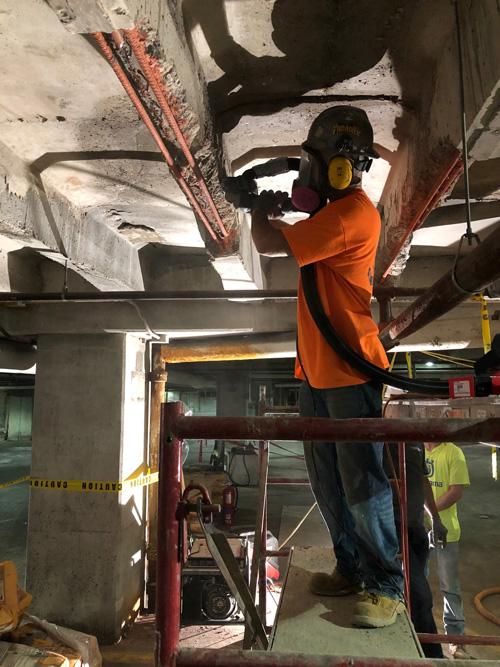 Construction worker removing concrete debris