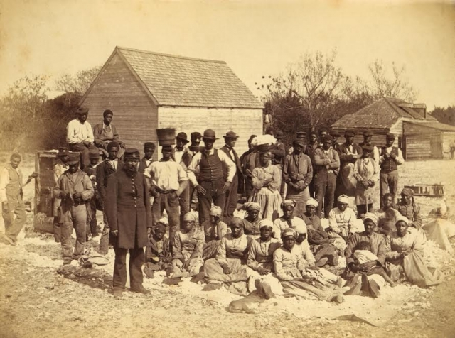 A Union soldier stands with African Americans on the plantation Thomas F. Drayton, Hilton Head Island, South Carolina, 1862. Photo by Henry P. Moore, May 1862 (photo credit Everett Historical)