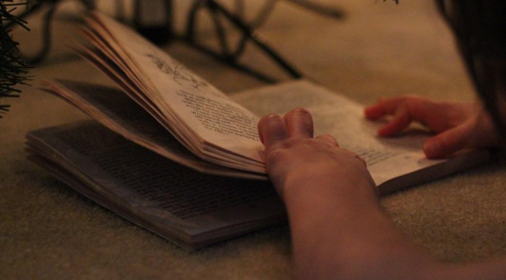 child reading under Christmas tree
