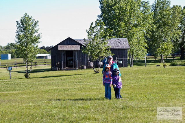 A mom and two kids in front of a log cabin | Ingalls Homestead