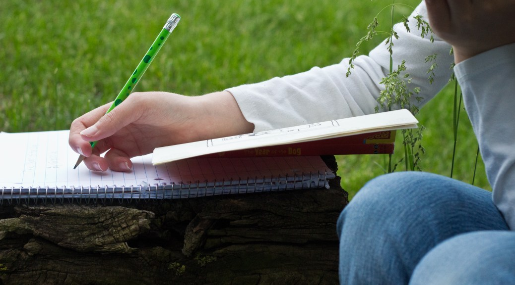 child writing outdoors
