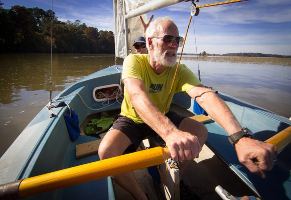Bill rowing the grass mini sailboat on the river