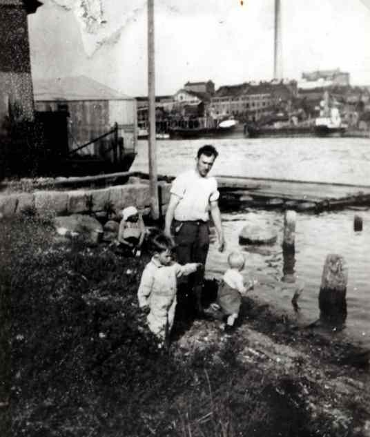 """Først på 1940-tallet var """"Trip"""" ikke lenger i drift, og Hauge-brygga var vanskelig tilgjengelig. Elvebredden var likevel et møtested. Rolf Edvardsen tar en tur med sin lille sønn og en kamerat, og """"Marie i bryggerhuset"""" har tatt med sine sotete kjeler for å rengjøre dem i elvesanden. En huspram ligger inntil brygga. Tvers over elva ligger to lektere til kai ved Torp bruk."""