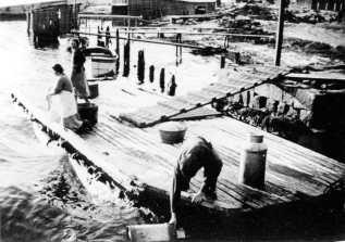 Dette bildet fra 1937 gir et godt inntrykk av hvordan befolkningen brukte Hauge brygge. Anker Johansen henter vann til kjøpmann Aimar Olsen i store melkespann. Margit Johansen (f. 1897) er tilskuer mens en ukjent kvinne på kne ved en avskjæring skyller klær i elva. Bølgetoppene som nærmer seg brygga, forteller at en båt nettopp har passert. Klesskylling og skuring av filletepper var et daglig syn. Om vinteren måtte husmødrene legge tykke lag med aviser på bryggekanten for ikke å fryse fast. Når de kom hjem, måtte de helle kokende vann på klærne for å tine dem. Mang en informant husker hvorledes de bar vann med åk og bøtter fra Glomma. Hauge Prambyggeri skimtes så vidt i bakgrunnen. Derfra hadde barna en fin badeplass om sommeren, og det var fisk å få. Fotograf: Helge Johansen. (Østfold Fylkes Billedarkiv). Forskjellige informanter til Birgit Holmen.