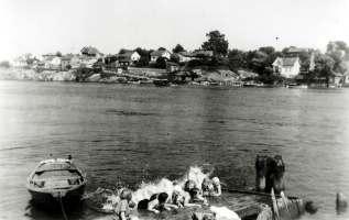 """Vannet i Glomma var ikke verre på 1950-tallet enn at det innbød til en dukkert. Torpeberget ligger på motsatt side, og vi ser veien som fører ned til """"Trippebrygga"""". Robåten var nyttig når ungdommene fra Rolvsøy skulle på fest på Torp. Den ble benyttet i tømmeret og for personbefordring. Foto: Sven Ørebæk"""