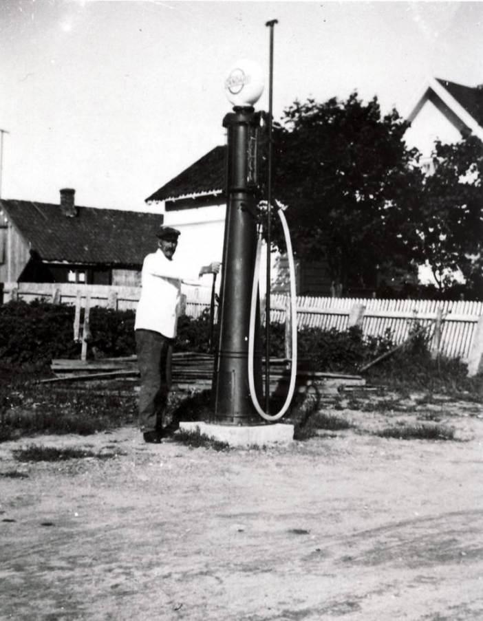 Da bilen gjorde sitt inntog fant landhandlerne å ville utvide varesortimentet. Enhver landhandler med respekt for seg selv hadde en bensinpumpe i veikanten utenfor butikken. Landhandleriene lå i kort gangavstand fra hverandre. Det gjorde også bensinpumpene. På bildet demonstrerer kjøpmann Marius Martinsen i Soliveien 8 på Rekustad hvordan han pumper opp bensinen fra en nedgravd tank til en kuppel på toppen av pumpa. Kilde: Rolvsøy bygdebok. S.455.