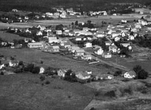 """Evje med Svaneveien – et flyfoto Etter andre verdenskrig skjedde en betydelig boligreisning på Rolvsøy. Deling av gamle eiendommer skaffet billig tomter. Rundt 1950 fikk Evje kommunal vann- og kloakktilknytning. Et område nær grensen mot Hauge ble regulert for boliger. Planleggingen var interessant. Boligene ble plassert side om side langs en vei, som skulle få navnet Svaneveien. At det skulle bli behov for garasjeplass var utenkelig. Å anlegge en snekkerfabrikk kloss inn til boligstrøket var å sikre arbeidsplasser i nærmiljøet. Øverst til venstre i bildet ligger boligfeltet i Svaneveien. Her går det frem at veien fører frem til Glomma. Noenlunde samtidig med utbyggingen av boligfeltet reiste ESSO et tankanlegg på gamle Evje teglverks grunn. Tankbilene kjørte over jernbanelinjen på Evje, gjennom boligstrøket og ned til tankanlegget. Datidens politikere hadde opplevd """"de harde tredveåra"""". For dem var det en oppgave å sikre inntekter til kommunen, og skaffe befolkningen gode boliger og sikre inntekter. Miljø og sikkerhet var ukjente begreper på denne tiden. Da Evjebekkveien ble anlagt i de senere år, ble boligområdet igjen rolig og hyggelig."""