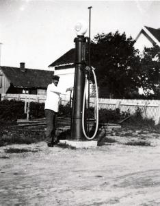"""Med bilismens fremvekst på 1920-tallet oppsto behovet for drivstoff. Bensin ble en selvfølgelig del av landhandlernes varetilbud. Her viser Marius Martinsen frem sin """"Standard"""" bensinpumpe. Landhandlerne lå tett i området rundt broa. Det samme gjorde bensinpumpene."""