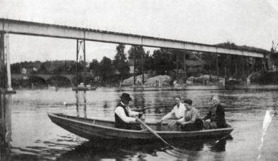Smed Syver Bjørnstad på rotur under jernbanebroa en søndag tidlig på 1920-tallet. Kanskje ser vi familien komme hjem etter et besøk på Greåker. Den første Rolvsøysund bro synes i bakgrunnen, så det ville vært enkelt å ta veien over broa. Men det var sikkert hyggeligere med en rotur. Foto: Rolvsøy bygdebok